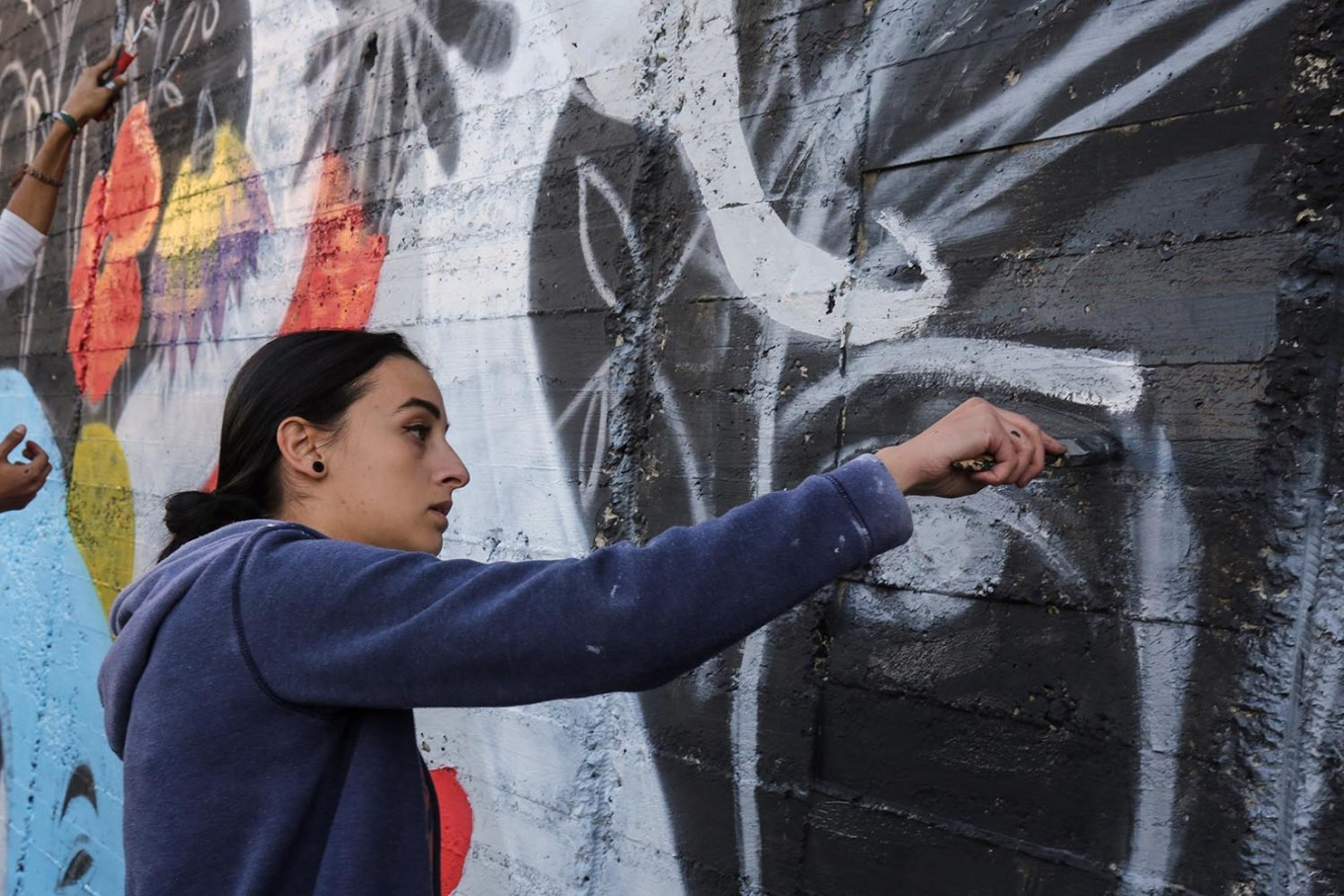Suha Sultan, a 20-year-old graffiti artist and student, uses a brush to draw a mural on a wall in the Jordanian capital Amman on December 16, 2017.