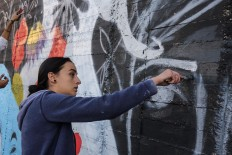 Suha Sultan, a 20-year-old graffiti artist and student, uses a brush to draw a mural on a wall in the Jordanian capital Amman on December 16, 2017. A tiny group of graffiti artists are on a mission -- daubing flowers, faces and patterns across the capital Amman to bring more colour to the lives of its four million inhabitants. In a conservative society like Jordan's, the graffiti artists have constantly had to challenge convention to carve out a niche for their works, though still with limits as they steer away from politics and religion. AFP/Khalil Mazraawi
