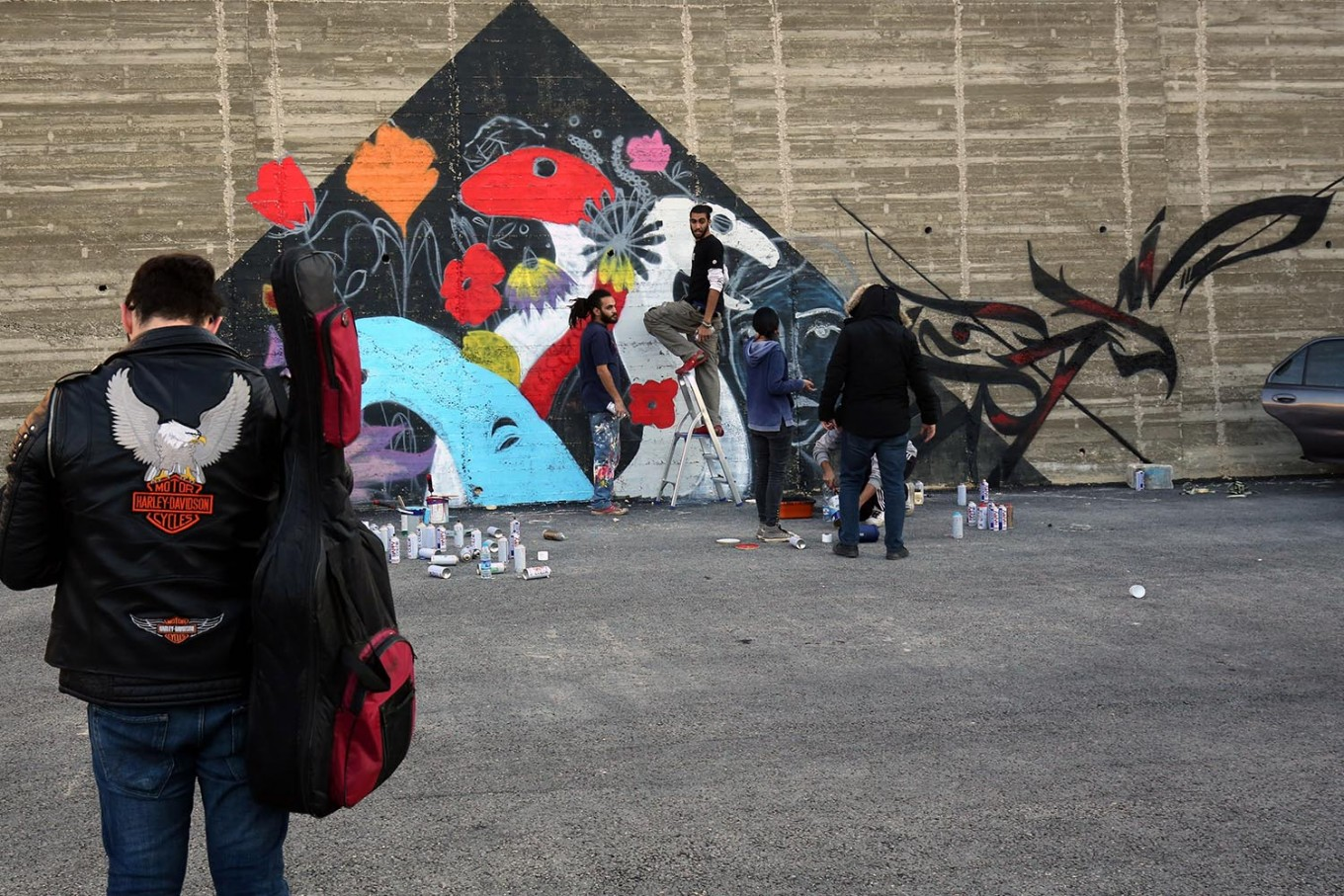 A picture taken on December 16, 2017 shows graffiti artists drawing a mural in the Jordanian capital Amman. A tiny group of graffiti artists are on a mission -- daubing flowers, faces and patterns across the capital Amman to bring more colour to the lives of its four million inhabitants.