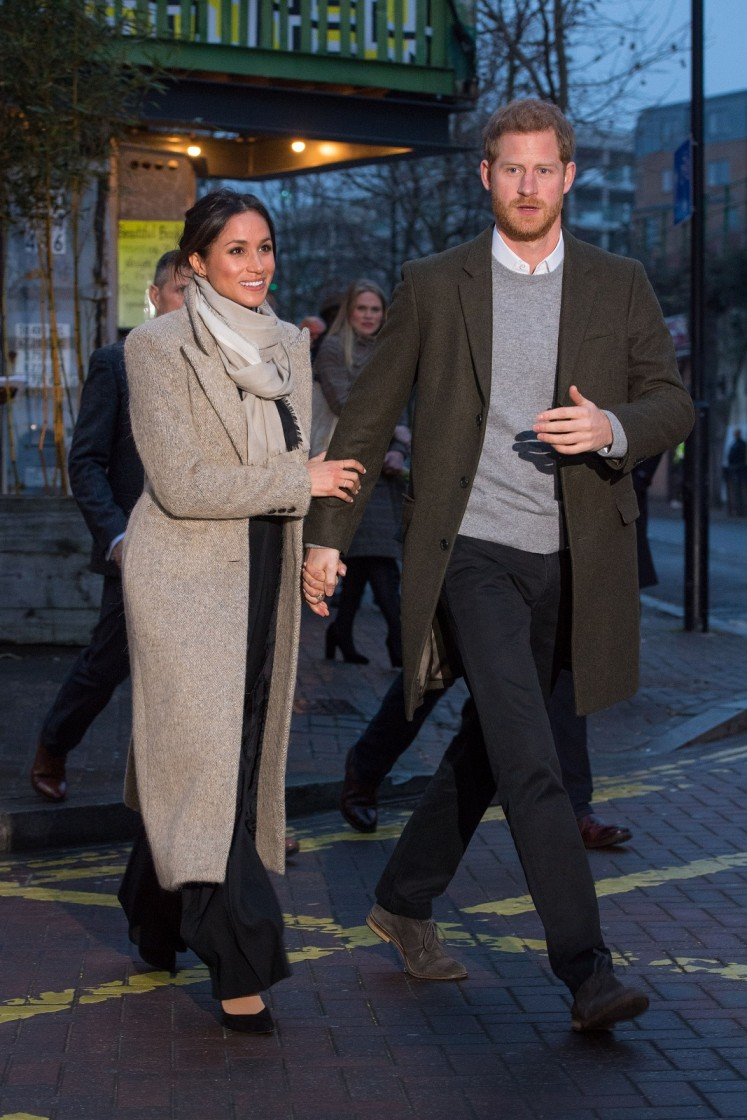 Britain's Prince Harry (R) and his fiancée, US actress Meghan Markle walk out to meet well-wishers as they leave after a visit to Reprezent 107.3FM community radio station in Brixton, south west London on January 9, 2018.