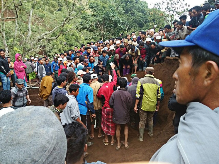 Rescue efforts: Residents help evacuate victims of the landslide on Wednesday.