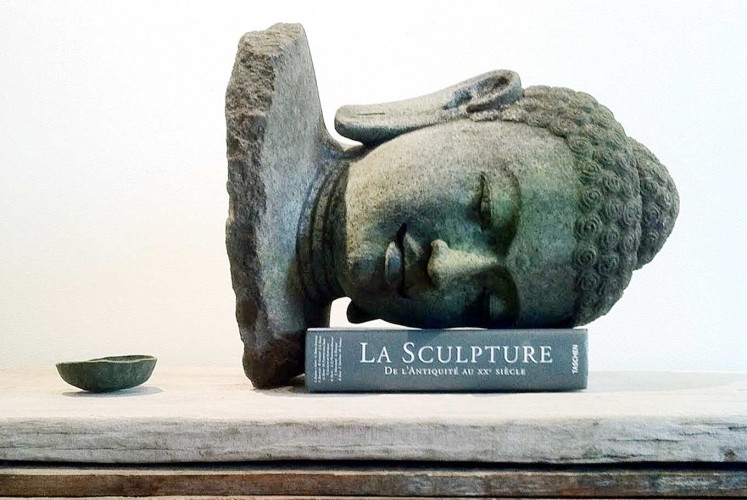 The imitation of the Buddha head as a book holder that Indonesian-born artist Ari Bayuaji created is a symbol of how meaningless the original pieces are if not placed in their rightful place.
