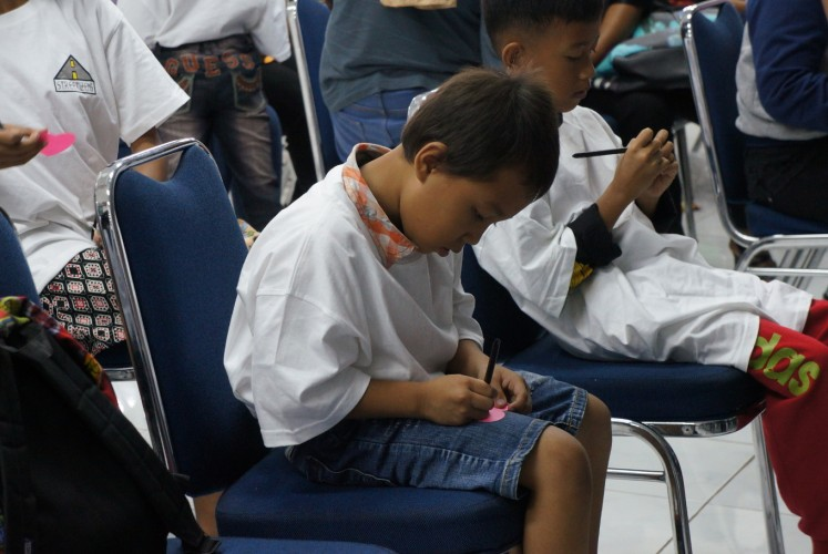 A child that was invited to Streetizens' New Year's Celebration event at Wisma ADR in Penjaringan, North Jakarta, on Jan. 13 writes his wish for the new year on a piece of heart-shaped paper.