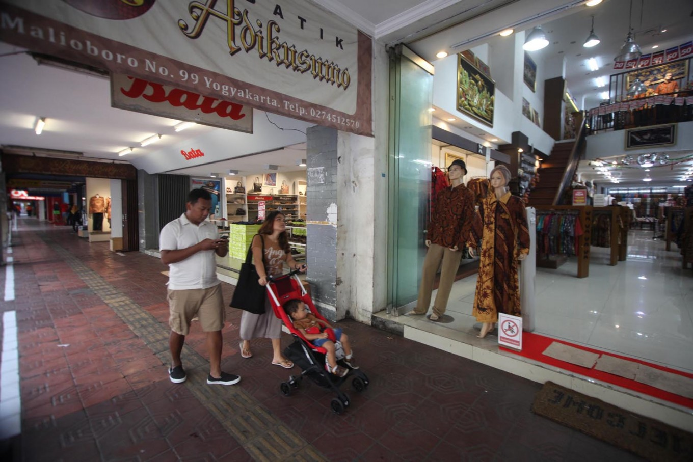A family strolls down a sidewalk on Malioboro, which is usually occupied by street vendors. JP/Boy T. Harjanto