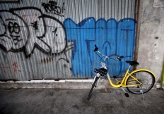 A yellow bicycle is seen parked on an empty sidewalk. JP/Boy T. Harjanto