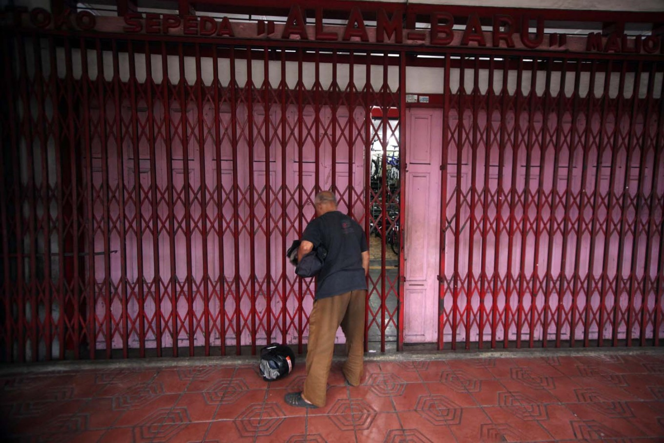 A shop attendant closes a store gate in the afternoon. JP/Boy T. Harjanto