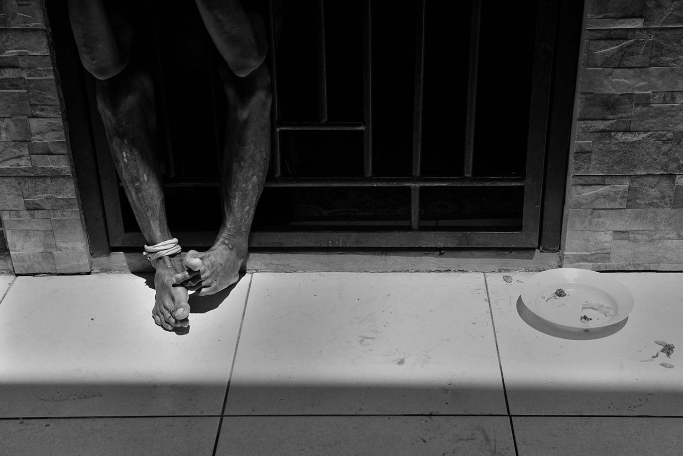 A mentally ill patient rests his feet through the bars of his isolation room in the Galuh Foundation rehabilitation center in Bekasi, West Java. Antara/Hafidz Mubarak