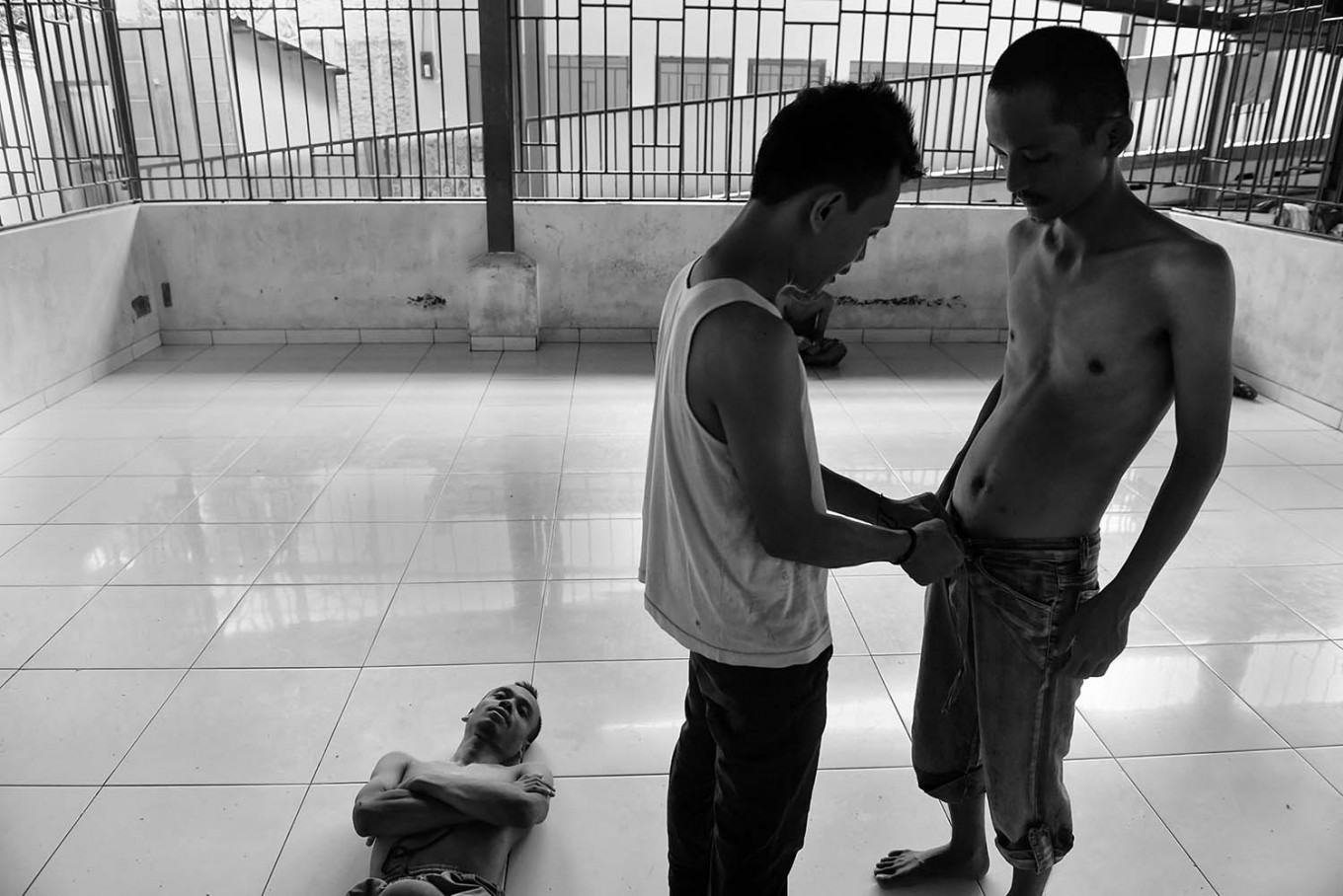 A nurse helps a patient put on his pants while another lies on the floor. Antara/Hafidz Mubarak