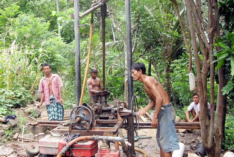 Raising water: Residents operate a water well drilling rig to access safe drinking water.