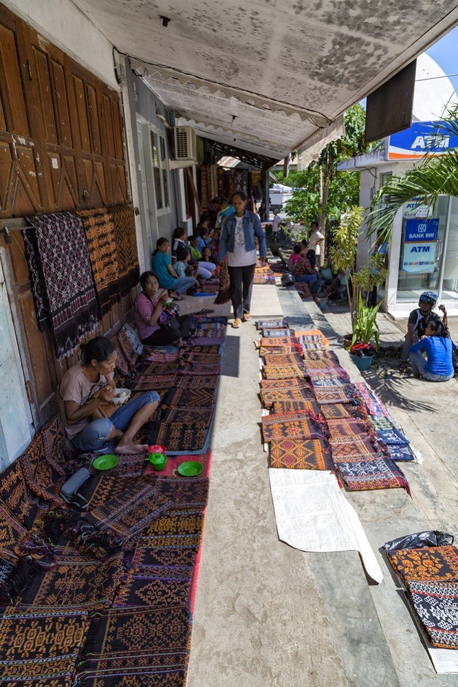 Merchants selling traditional fabrics in Maumere market.