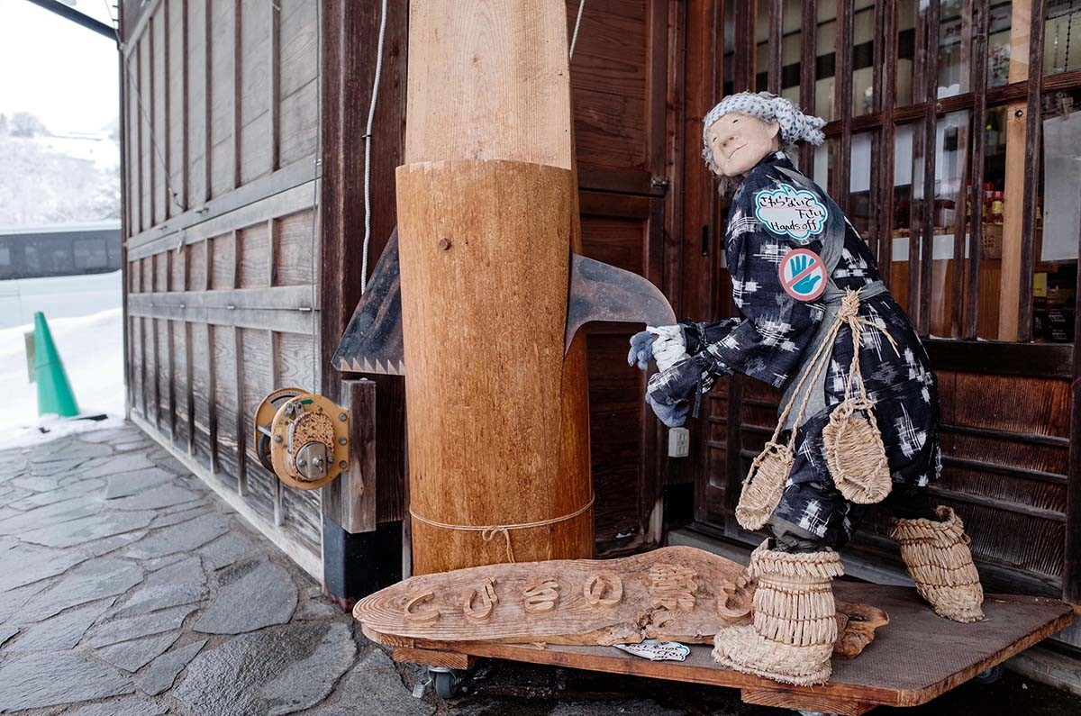A wooden statue of a lumberjack in front of a souvenir shop welcomes tourists in Shirakawa-gō. JP/Anggara Mahendra