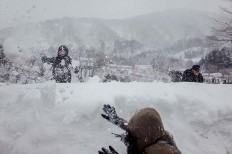 Visitors play in the snow at Shirakawa-gō. JP/Anggara Mahendra