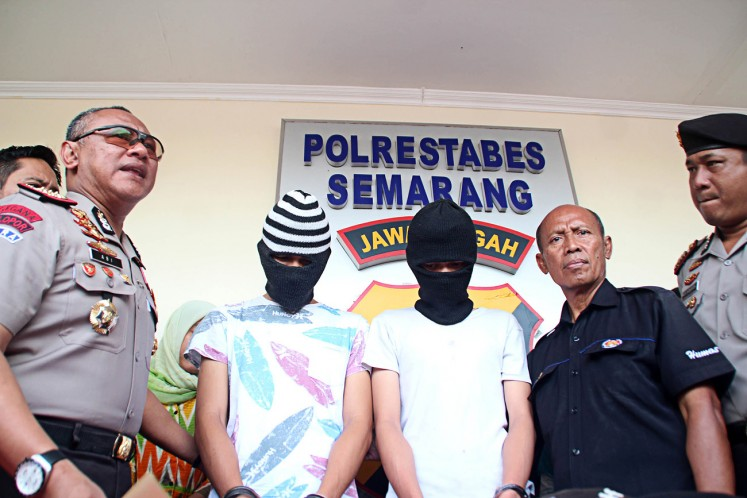 Suspects: TA and IB appear at a press conference at the Semarang Police office on Tuesday. They are accused of murdering an online taxi driver in the city.