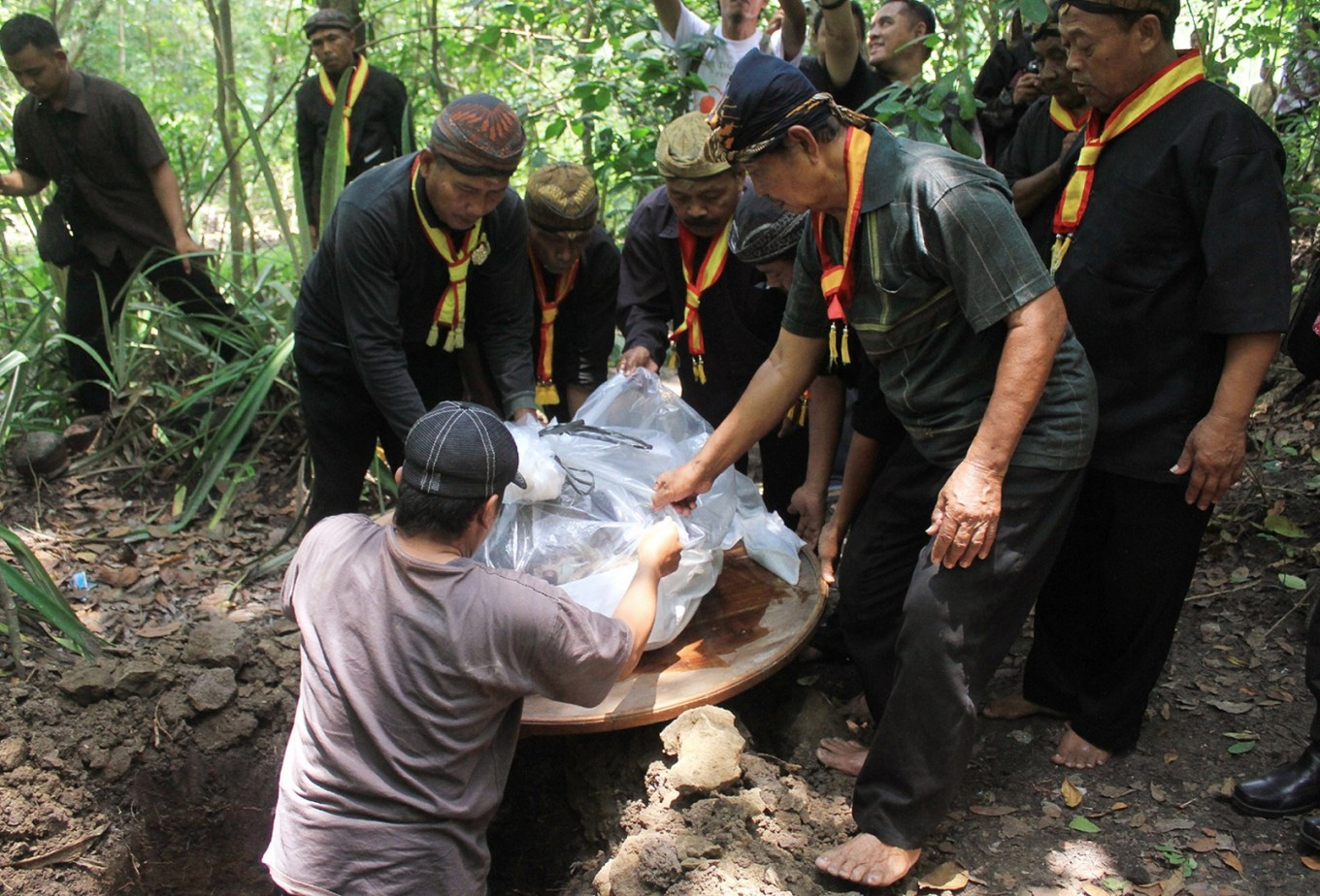 'Abdi dalem' plant a buffalo head as the main offering to the forest.