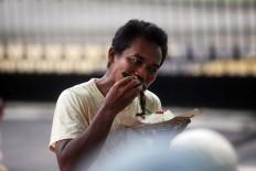A man bites into his fried catfish. JP/ Boy T. Harjanto