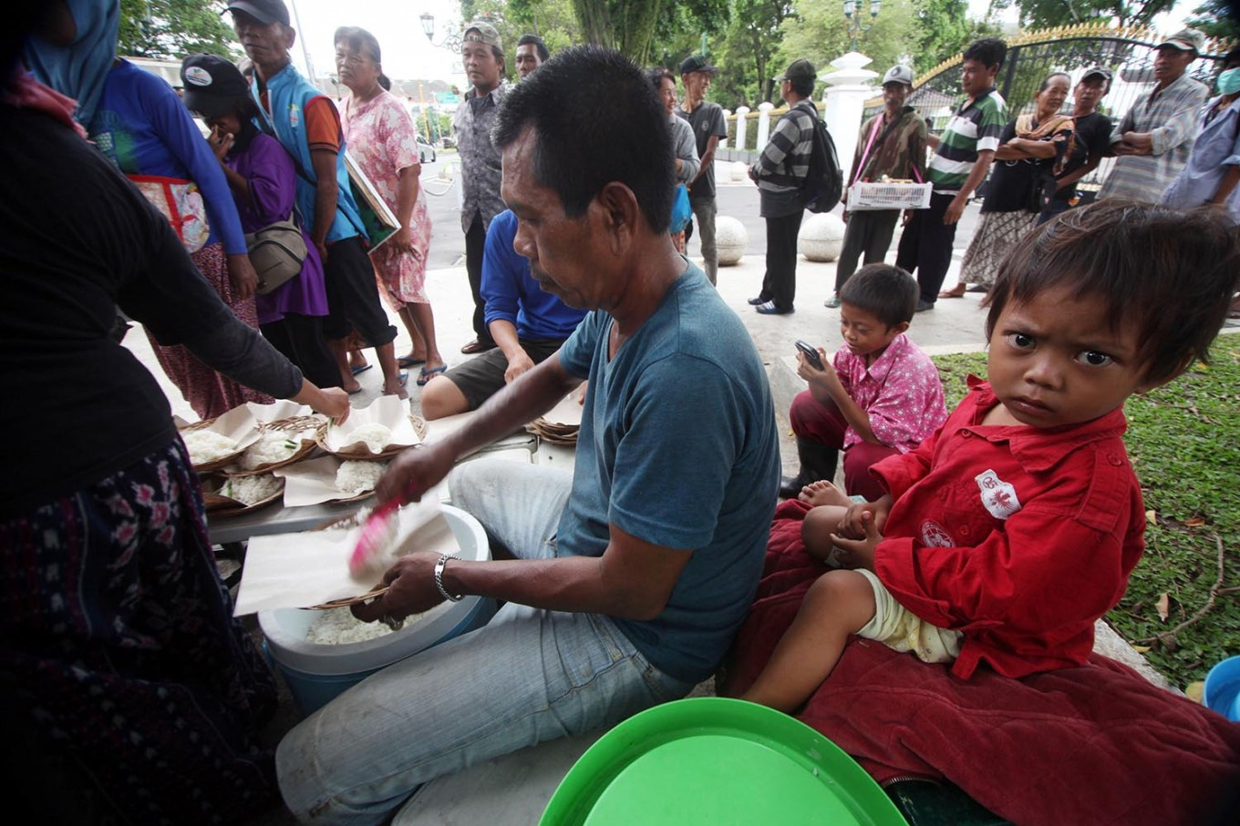 A volunteer serves a portion of white rice for the free meal. JP/ Boy T. Harjanto