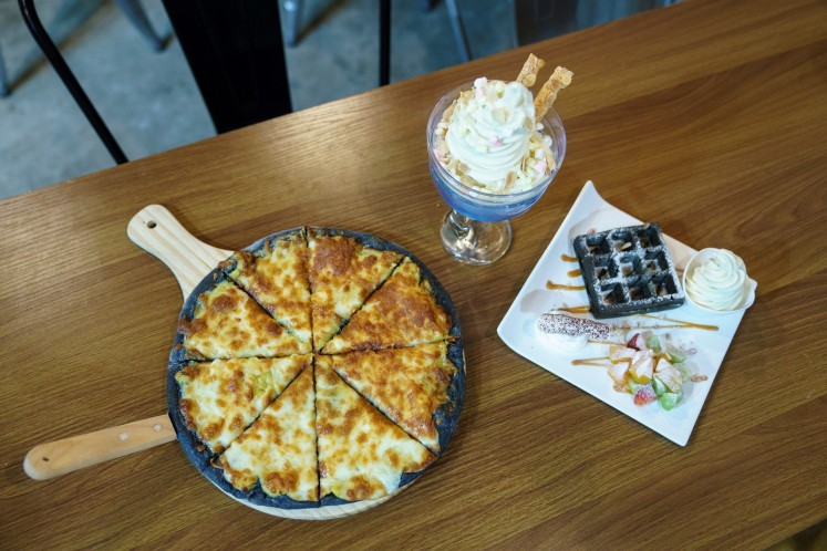 This photo taken on January 24, 2018 shows various dishes including durian flavoured ice cream, waffles and pizza at Mao Shan Wang cafe in the Chinatown district of Singapore.
