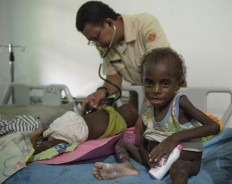 """A member of an Indonesian military task force checks child at a local hospital in Agats, the capital of Asmat district in Indonesia's easternmost Papua province, on January 26, 2018. Some 800 children have been sickened in the area with as many as 100 others, mostly toddlers, feared to have died in what a military official called an """"extraordinary"""" outbreak that was first made public this month. AFP/ Bay Ismoyo"""