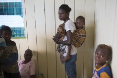 A Papuan woman and their children wait for medical treatment at local clinic at Ayam village in Asmat district in Indonesia's easternmost Papua province on January 26, 2018. Some 800 children have been sickened by a measles-and-malnutrition outbreak in Indonesia's remote Papua province, officials said January 25, with as many as 100 people, mostly toddlers, feared to have been killed in the outbreak. AFP/ Bay Ismoyo