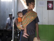 A Papuan woman carries her child to a local hospital handling measles and malnutrition patients in Agats, the capital of Asmat district in Indonesia's easternmost Papua province, on January 25, 2018. Some 800 children have been sickened by a measles-and-malnutrition outbreak in Indonesia's remote Papua province, officials said January 25, with as many as 100 people, mostly toddlers, feared to have been killed in the outbreak. AFP/ Bay Ismoyo