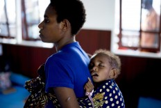 A Papuan mother carries her sleeping child on her back at a temporary hospital handling measles and malnutrition patients in Agats, the capital of Asmat district in Indonesia's easternmost Papua province, on January 25, 2018. Some 800 children have been sickened by a measles-and-malnutrition outbreak in Indonesia's remote Papua province, officials said January 25, with as many as 100 people, mostly toddlers, feared to have been killed in the outbreak. AFP/ Bay Ismoyo