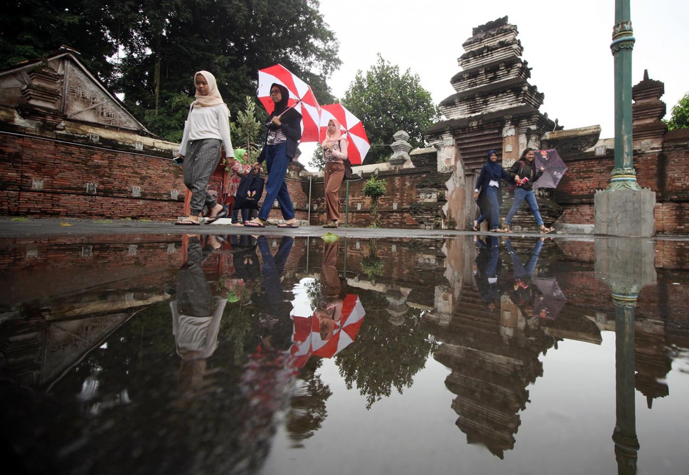 Visitors are using umbrellas to cover themselves from the rain. JP/Boy T. Harjanto
