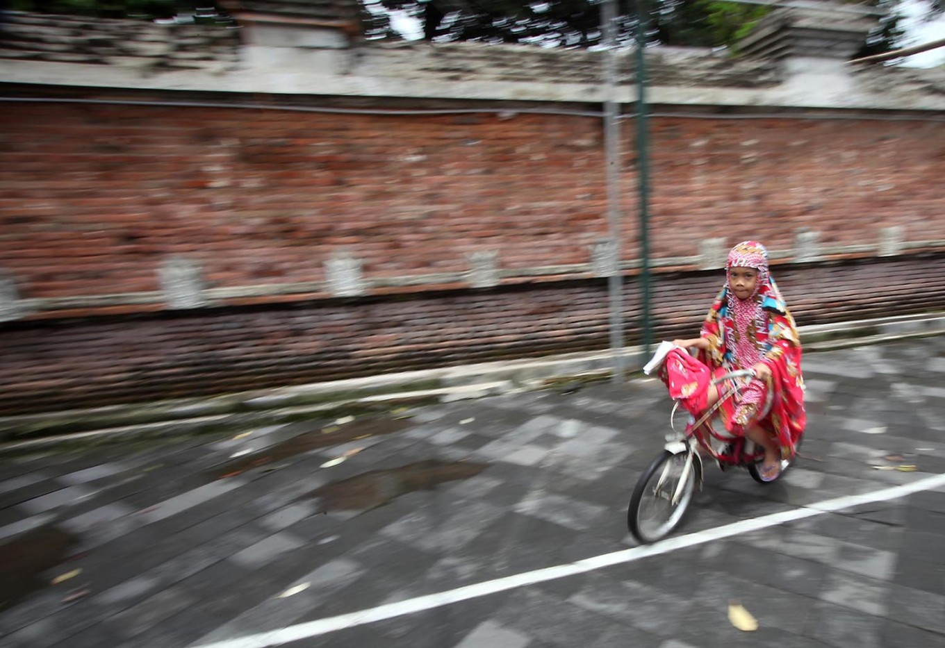 A girl rides her bike in the mosque's compound after performing the midday prayer. JP/Boy T. Harjanto