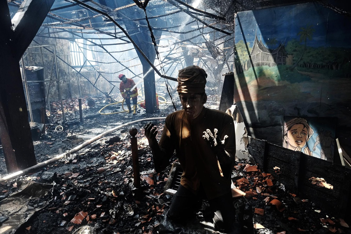 A fire fighter puts out fires among the debris inside the 17th century Dutch colonial building that houses the Maritime Museum in Penjaringan, North Jakarta on Tuesday January.16. Although the blaze destroyed the museum's collection, including dioramas and historic maps, no casualties were reported from the incidents. JP /Jerry Adiguna