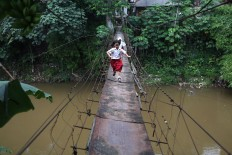 Schoolchildren run across a bridge in Srengseng Sawah, South Jakarta on Tuesday, January. 23. The bridge, which is in poor condition, serves as a main access point for residents in the area. JP/Seto Wardhana.