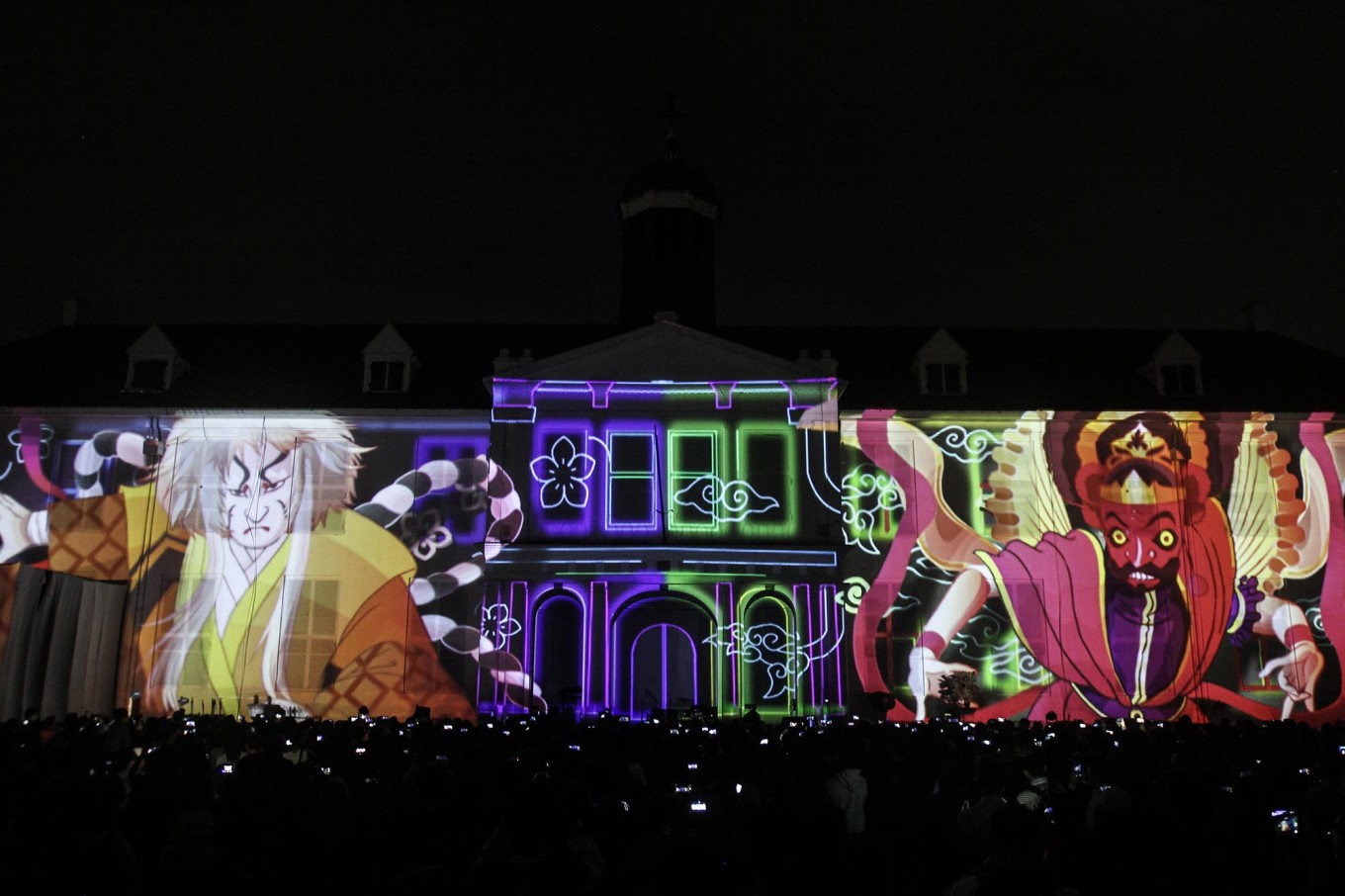 People watch images from video mapping reflected on the wall of Fatahillah Museum in Kota Tua, Central Jakarta, as Indonesia and Japan comemmorate 60 years of bilateral relations on Friday, January. 19. The event was attended by Japanese special envoy Toshihiro Nikai. JP/Ben Latuihamallo