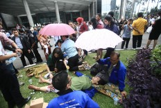 Injured victims receive medical treatment following the collapse of a mezzanine floor inside the Indonesia Stock Exchange (IDX) building in Jakarta on Monday, January. 15. At least 75 people were reportedly injured when the mezzanine fell into the lobby. JP/Dhoni Setiawan