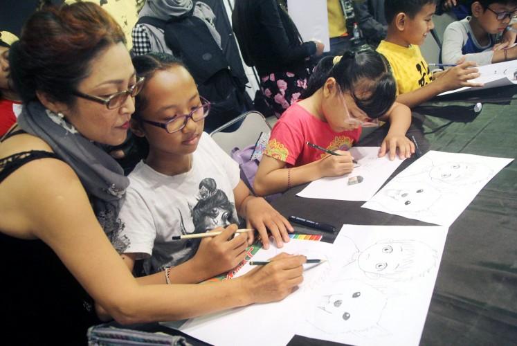 Cultivating creativity: Japanese manga artist Tamiko Tsuneoshi teaches children how to draw during a manga workshop at Bentara Budaya Bali on Saturday.