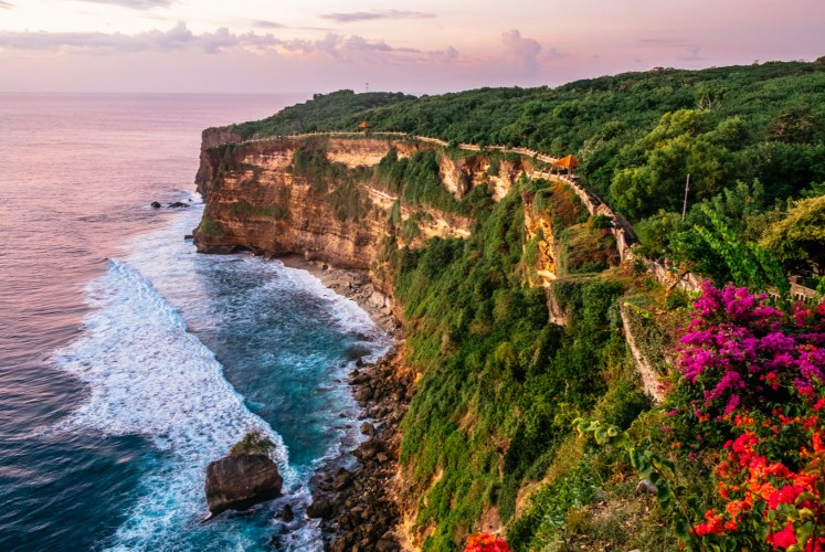 Sunset casts a rosy hue over the cliffs of Uluwatu in southwestern Bali.
