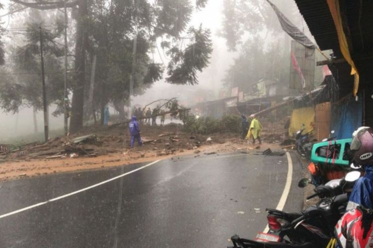 Some officers work on fallen trees blocking the road in Puncak, Bogor, West Java, on Monday.