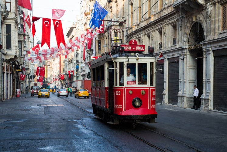 A classic tram passes through Istanbul's popular Taksim Square.