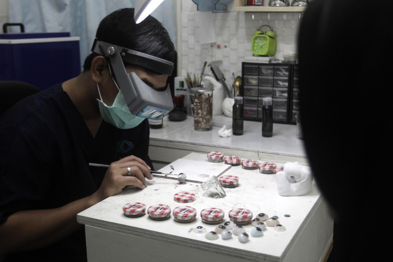 Work of art: Rizwan paints an artificial ey in front of his patient. JP/ Ben Latuihamallo