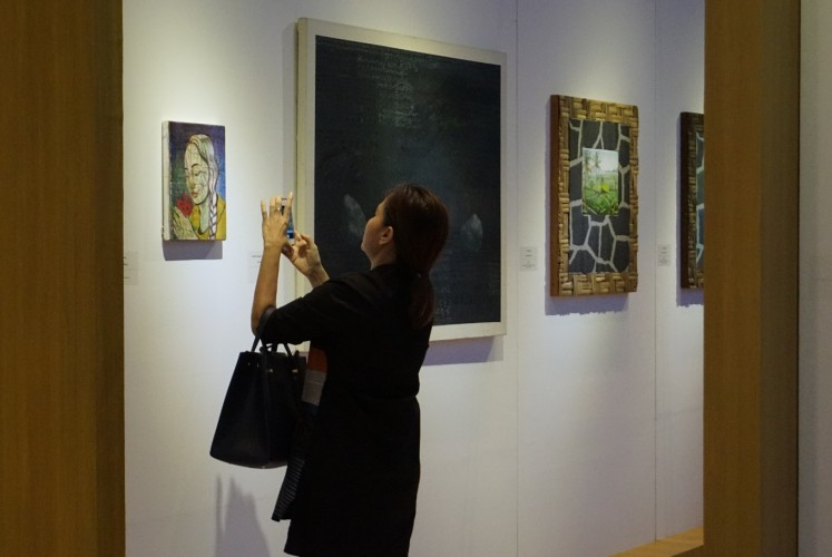 A visitor marvels at one of the paintings displayed at the