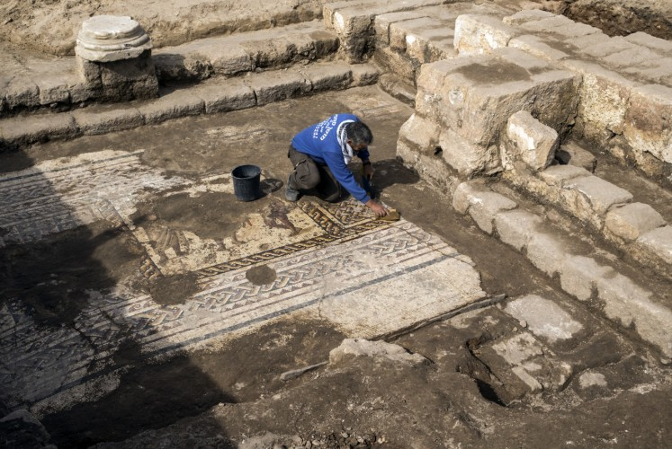 Workers from the Israeli Antiquity Authority (IAA) clean a rare Roman mosaic from the 2nd–3rd centuries at the Israeli Caesarea National Park on February 8, 2018. According to Dr. Peter Gendelman and Dr. Uzi 'Ad, directors of the excavation for the IAA: 'This colourful mosaic, measuring more than 3.5 x 8 meters, is of a rare high quality. It features three figures, multicoloured geometric patterns and a long inscription in Greek.'