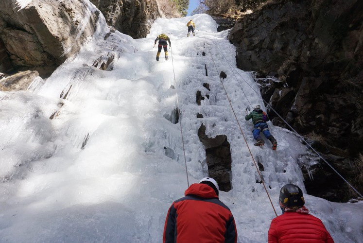 Climbers scale an ice cliff.
