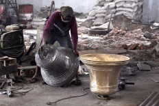 A worker moves a 170 kg bronze bell to be polished. The price of the bell is Rp 65 million. JP/Magnus Hendratmo