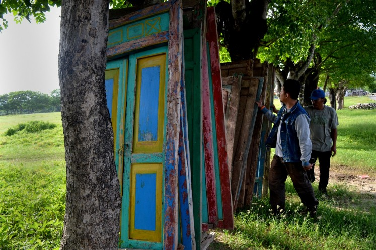An antique dealer shows old doors of Madurese houses to a potential buyer.