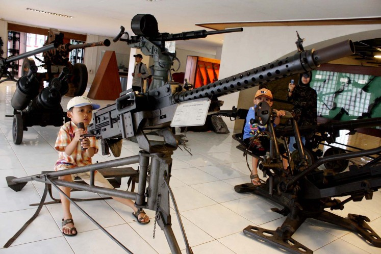 Two kids play with old heavy machine guns once used by the Indonesian Military (TNI) at the Satria Mandala military museum in Jakarta on Sunday. As apart of the celebration of TNI.