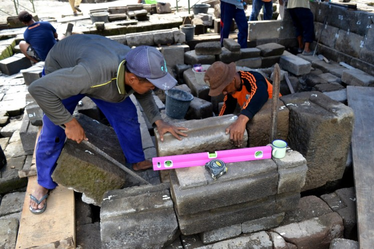 Members of the special anastylosis team reassemble the temple structure at a location adjacent to the Kedulan site. Once their placement has been determined and confirmed, the blocks will be moved to the actual site to  reconstruct the temple, block by block.