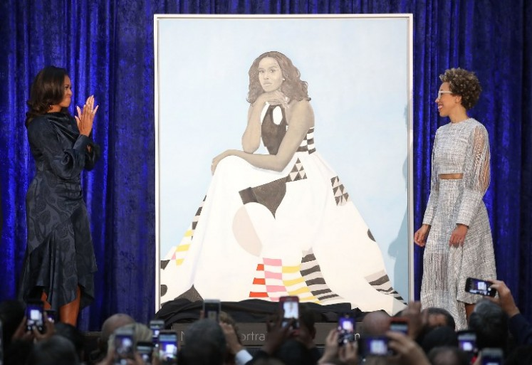 WASHINGTON, DC - FEBRUARY 12: Former U.S. first lady Michelle Obama (L) and artist Amy Sherald unveil her portrait during a ceremony at the Smithsonian's National Portrait Gallery, on February 12, 2018 in Washington, DC. The portraits were commissioned by the Gallery, for Kehinde Wiley to create President Obama's portrait, and Amy Sherald that of Michelle Obama.