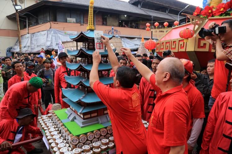 Sticking prayer papers on 'kue keranjang' mounds to be prayed upon in Tien Kok Sie Temple, Pasar Gede, Surakarta.
