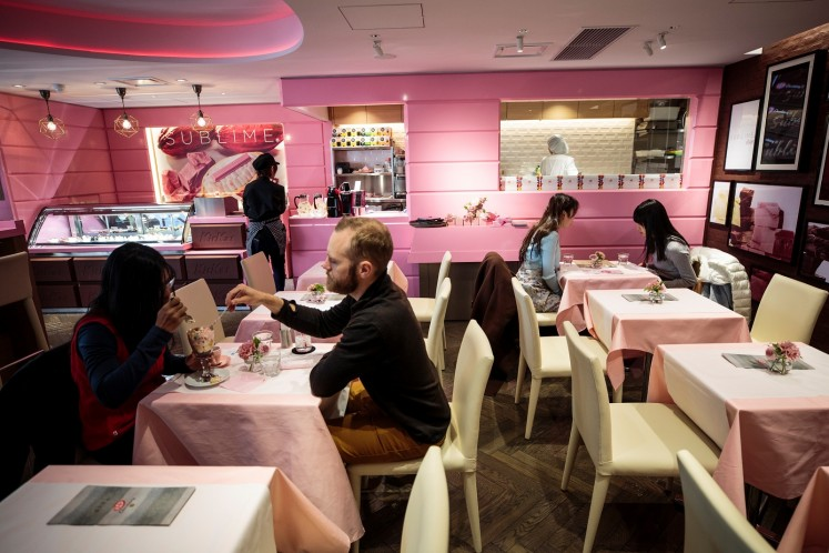 In this picture taken on February 7, 2018, tourists from Australia, Ayndri de Soysa (L) and Andrew Frain (2nd L), have an ice cream at a KitKat chocolatory shop in Tokyo. It is a marriage made in Heaven for cute-obsessed Japan: this Valentine's Day, lovers can present the object of their affection with a world first -- naturally bright pink chocolate.