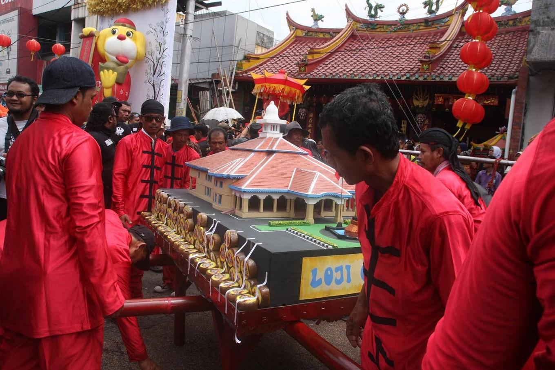 Home sweet home: Men carry a miniature Loji Gandrung decorated with kue keranjang (basket cake).   JP/ Maksum Nur Fauzan