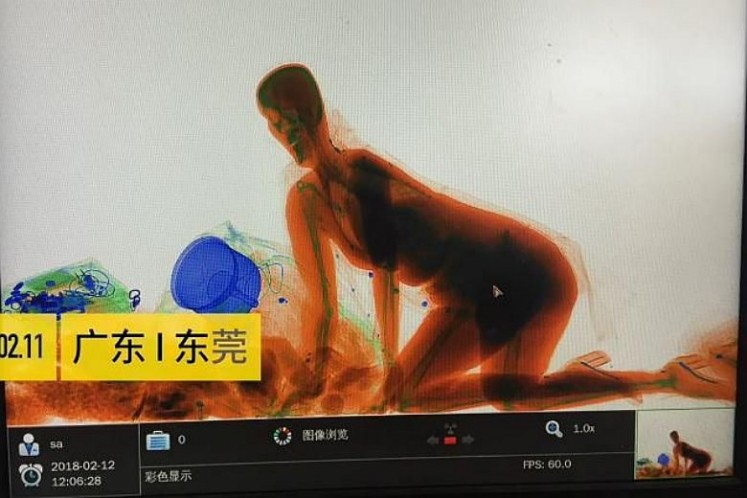 Woman refuses to leave handbag, climbs into X-ray machine at China station