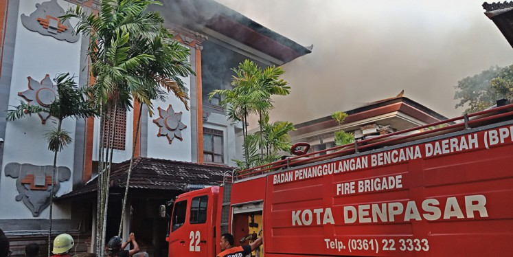 Damaged: Black smoke emanates from a building at the Bali governor's office complex on Feb. 13 as a fire truck attempts to extinguish the fire.