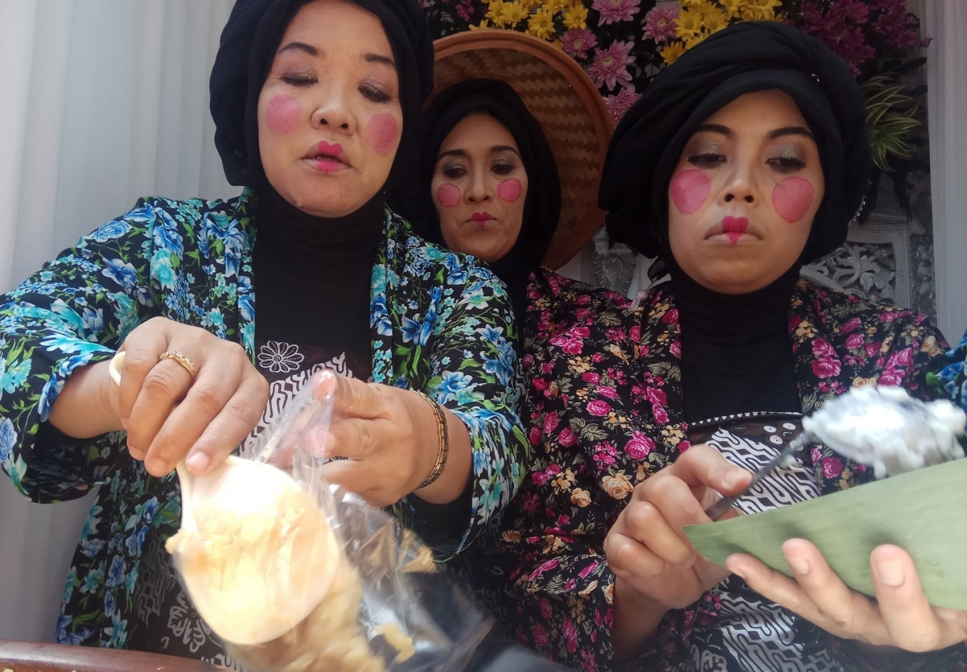 Members of a family welfare program wear make up to attract customers to their stand. As many as 27,300 'jenang' were given away for free during the festival.
